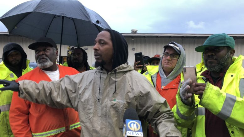 A gathering of santiation workers, mostly Black, standing outside a facility in their work gear giving an interview to a news reporter.